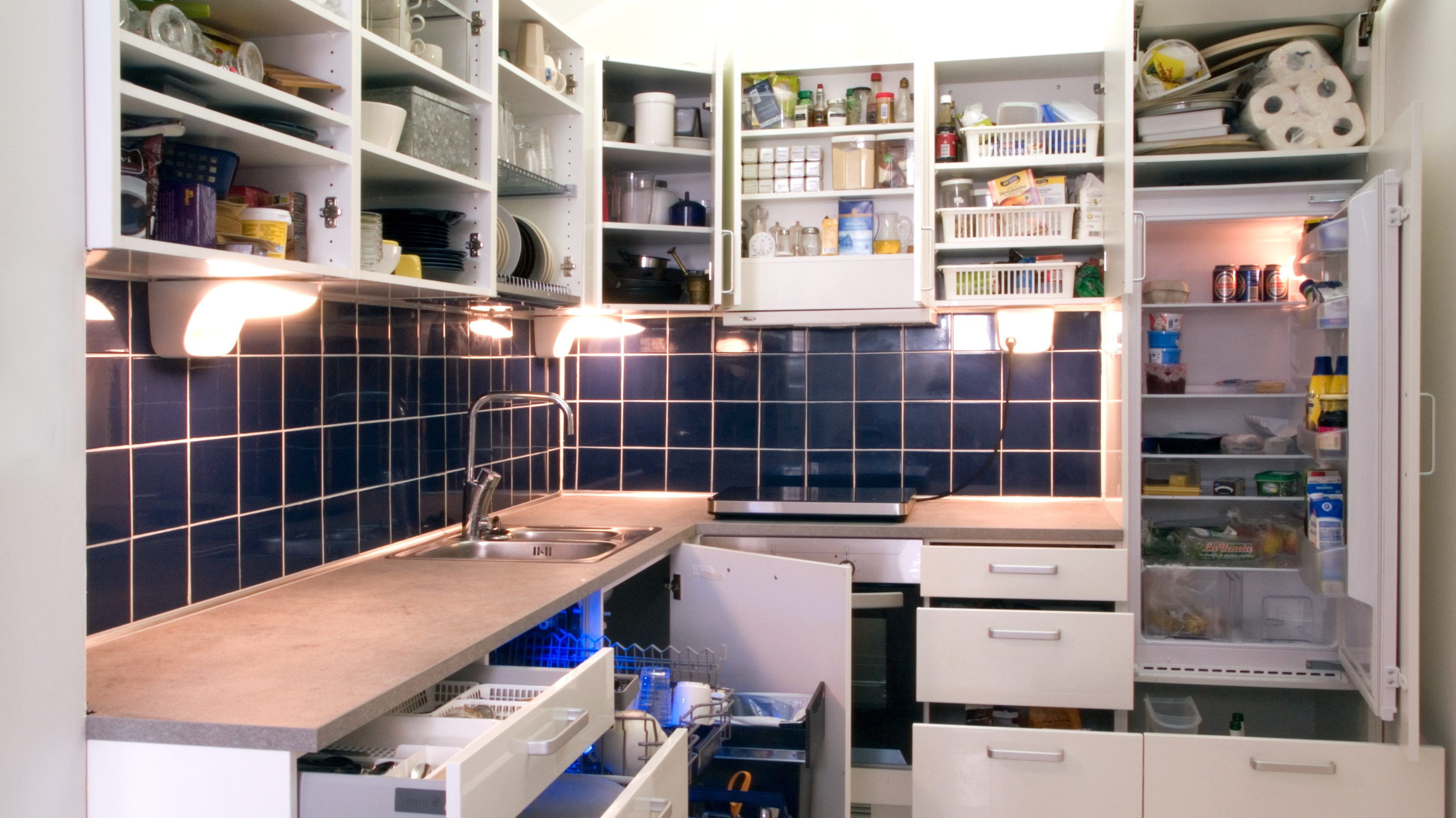 Simphome White kitchen with cabinet doors and drawers opened or removed so that real life stuff can be seen in cabinets